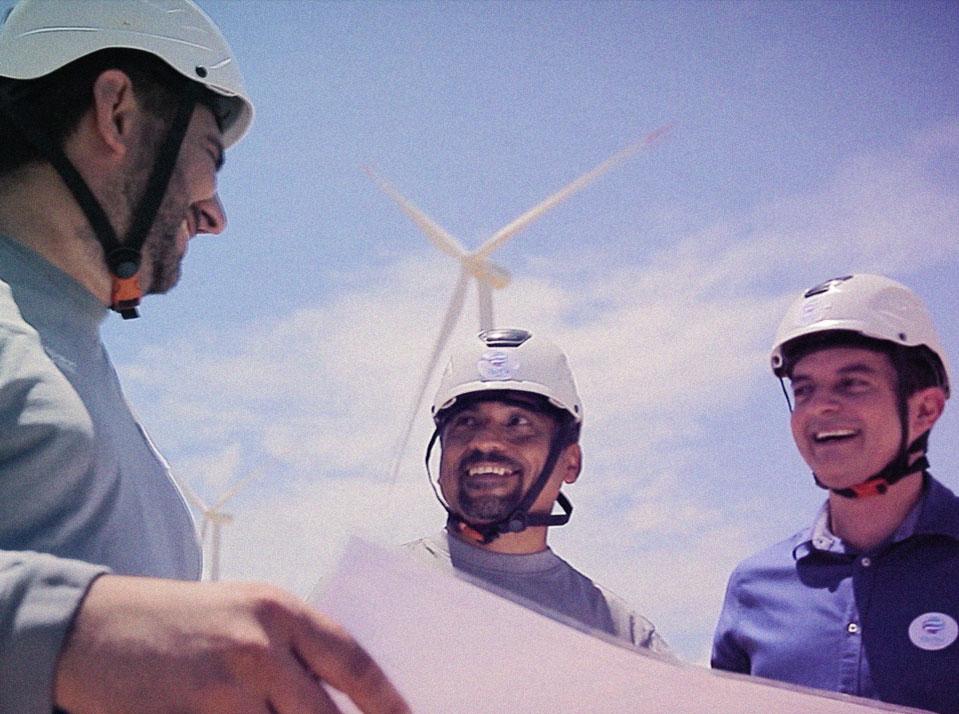 Três homes olhando uma planta de projeto e conversando